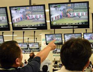 Journalists watch screens in the media centre showing …