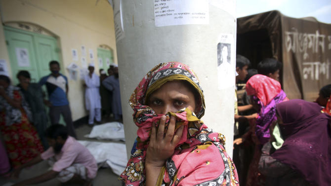 A woman covers her nose to block out the smell of decomposing bodies at a makeshift morgue where victims of the collapse of the garment factory buildings are brought Friday, May 3, 2013 in Savar, near Dhaka, Bangladesh. Authorities suspended the mayor of the suburb of Savar, where the building was located, and arrested an engineer who called for the building's evacuation last week but was also accused of helping the owner add three illegal floors to the eight-story structure. (AP Photo/Wong Maye-E)