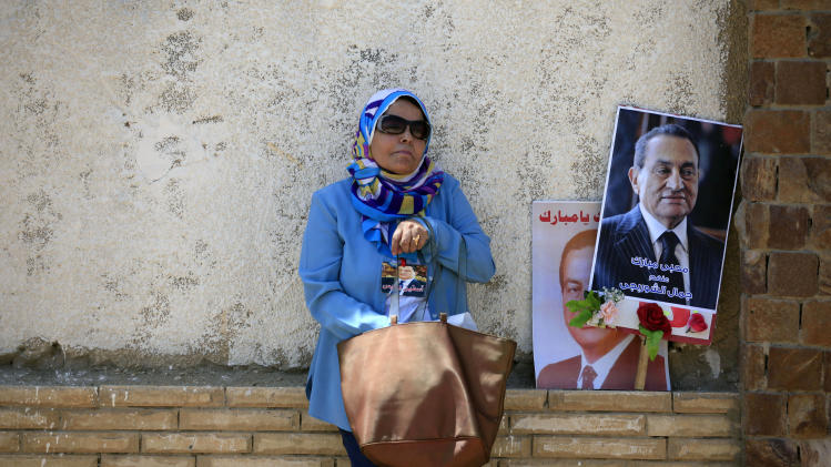 "A supporter of Egypt's ousted President Hosni Mubarak, pictured, attends a rally outside a courtroom in Cairo, Egypt, Saturday, May 11, 2013. Egyptian prosecutors say they are presenting new evidence in the retrial of Mubarak. The former president, all in white and wearing sunglasses, attended the hearing in the courtroom defendants' cage alongside his two sons and former interior minister, who was in charge of police at the time. Arabic writing on the poster at right reads, ""Jamal al-Shorbaji on behalf of Mubarak lovers."" (AP Photo/Khalil Hamra)"