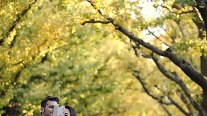 Couple takes a selfie beneath yellow ginkgo leaves in Tokyo