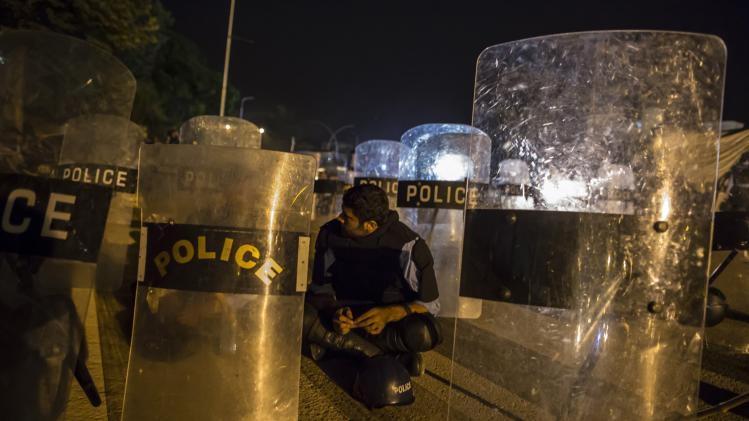"Police officers sit near their riot shields in front of the Parliament house building during the ""Revolution March"" protests in Islamabad"