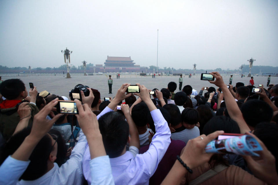 Tourists take photos of the flag raising ceremony on Tiananmen Square as they gather to mark the anniversary of the deadly 1989 crackdown on pro-democracy protestors, in Beijing, China, Monday, June 4, 2012.  (AP Photo/Ng Han Guan)