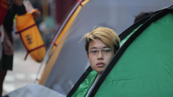 In this Saturday, Oct. 18, 2014 photo, a pro-democracy student protester peers out from his tent in the Mong Kok district of Hong Kong. Hong Kong riot police battled with thousands of pro-democracy protesters for control of the city's streets Friday night, using pepper spray and batons to hold back defiant activists who returned to a protest zone that officers had partially cleared. (AP Photo/Wally Santana)