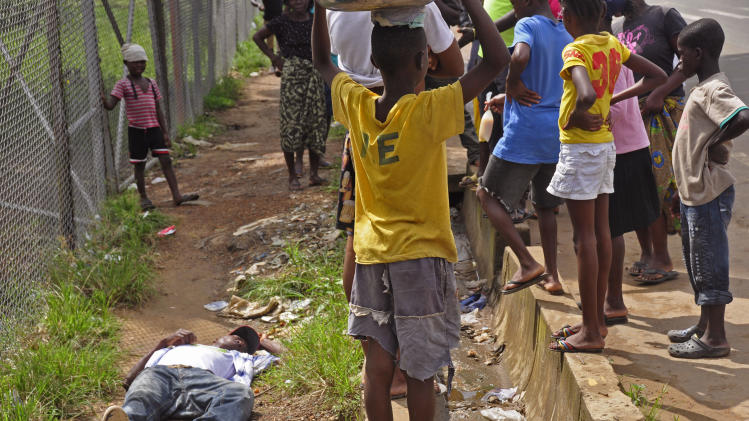 Children surround a man, left, that fell down while walking on a street suspected of having contracted the Ebola virus in the city of Monrovia, Liberia, Tuesday, Aug. 19, 2014. The World Health Organization says the outbreak has killed more than 1,200 people, while authorities struggle to contain its spread and treat the sick. (AP Photo/Abbas Dulleh)