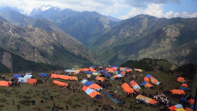 Local residents gather near their makeshift tents in Laprak village, Nepal's Gorkha district, on May 4, 2015