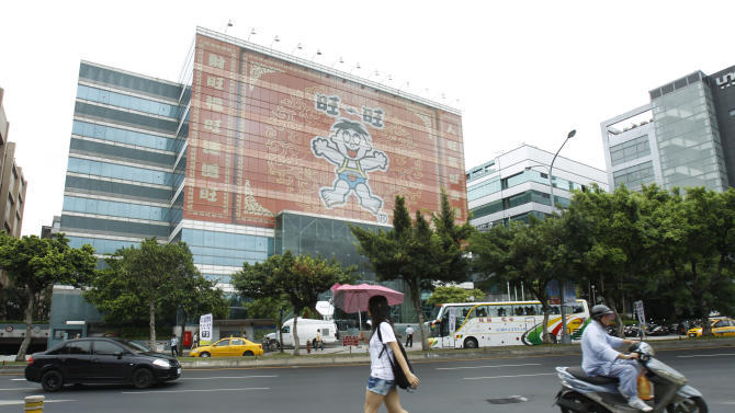 A pedestrian passes the Want Want China Times Group headquarters in Taipei, Taiwan, Thursday, July 26, 2012. Taiwan regulators have put strict conditions on a bid by the China-friendly Want Want China Times Group to purchase the island's largest cable TV system, amid growing concerns that China's commercial clout is already undermining freedom of the press in one of Asia's liveliest media markets. (AP Photo/Wally Santana)