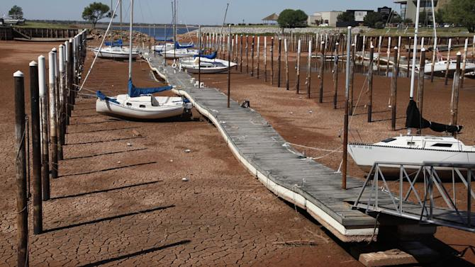 FILE - In this Sept. 30, 2011 file photo, sailboats and a floating dock lie on the dry, cracked dirt in a harbor at Lake Hefner in Oklahoma City. After recalculating data from 2011, the nation's climatologists are declaring that Oklahoma suffered through the hottest summer ever recorded in the U.S. last year — not Texas as initially announced last fall. (AP Photo/Sue Ogrocki)