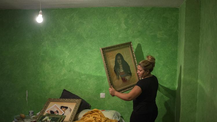 Fernando Montoya Jimenez's 32-year old daughter removes pictures from his room during his eviction in Madrid, Spain, Wednesday, July 23, 2014. Fernando Montoya Jimenez, 61, lived with his son Jesus Miguel, 14, and his 16-year old daughter Diana, who is six months pregnant, in an apartment owned by the Madrid Community state housing company for more than 20 years, paying subsidized rent. Jimenez who has a disability and epilepsy and has spent time in prison for prior convictions, lives from a state benefit of euro 311 (US$419) per month. The state housing company evicted him and his family after freezing his account with them when he failed to pay his rent. (AP Photo/Andres Kudacki)