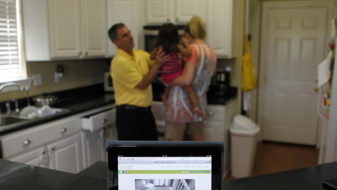 This Aug. 13, 2012, photo shows a webcam feed on an iPad of four-month-old Emily St. Martin in the Neonatal Intensive Care Unit at Ochsner Medical Center, at her family's home in LaPlace, La. Her parents, Laura and David St. Martin, with their daughter Jacqueline, 2, background, are able to watch her from a web cam installed over her crib on their iPad. (AP Photo/Gerald Herbert)