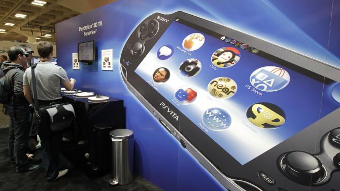 Sony PlayStation PS Vita is shown in foreground as attendees use the Sony PlayStation 3D TV SimuView in the Sony PlayStation booth at the Game Developers Conference in San Francisco, Thursday, March 8, 2012. (AP Photo/Paul Sakuma)