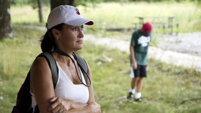 Ashley Hacker, of Franklin, Tenn., pauses, Saturday, July 7, 2012, in describing the ordeal she went through after the car she was traveling in with her husband and 12-year-old son Noah, right, was struck by falling trees during a powerful storm that tore through Great Smoky Mountains National Park near Townsend, Tenn., on Thursday evening. Rangers will soon reopen part of the Great Smoky Mountains National Park after violent storms caused the park to close. (AP Photo/Erik Schelzig)