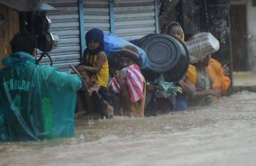 <p>Residents wade through a flooded street under heavy rain as they are evacuated from their homes in the village of Tumana, Marikina town, in suburban Manila on August 7, 2012. Torrential rains have brought the Philippines capital to a standstill, forcing at least 20,000 people to flee their homes as floodwaters covered half the sprawling city, authorities said.</p>