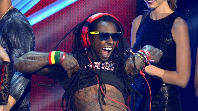 """FILE - In this Sept. 6, 2012 file photo, Lil Wayne accepts the award for best hip-hop video for """"Hyfr""""at the MTV Video Music Awards in Los Angeles.  The multiplatinum rapper was hospitalized on Friday night, March 15, 2013, and reps confirmed he was """"recovering."""" A person close to the superstar rapper's camp who asked for anonymity because of the sensitivity of the matter confirmed to The Associated Press that Lil Wayne had a seizure. (Photo by Mark J. Terrill/Invision/AP, File)"""