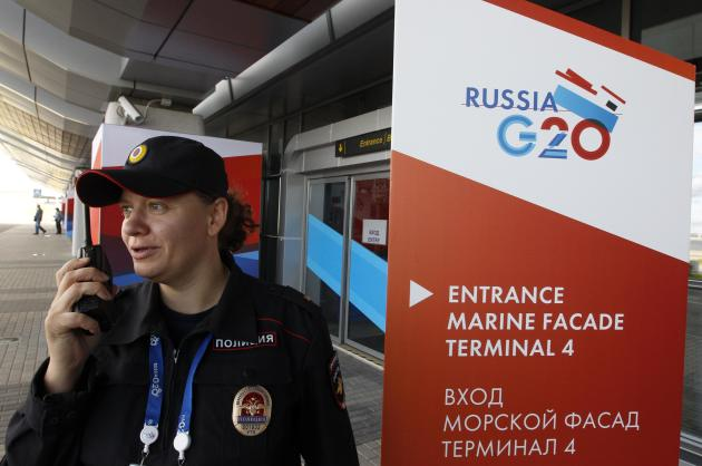 A policewoman speaks on a walkie-talkie near temporary signs for the G20 summit at the sea port in St. Petersburg