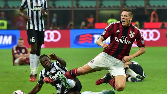 Juventus' Kwadwo Asamoah (L) fights for the ball with  AC Milan's Fernando Torres during their match in Milan on September 20, 2014