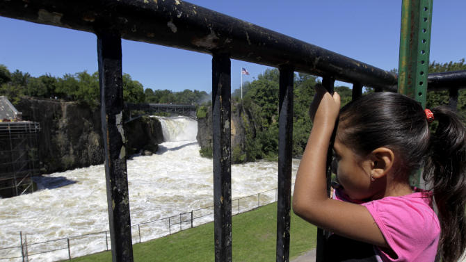 Jesery Gonzalez, 5, looks on as water rushes down the Great Falls as the Passaic River neared its cresting point following Hurricane Irene, Tuesday, Aug. 30, 2011, in Paterson, N.J. Many questions faced New Jerseyans as most rivers began to recede and expose a path of destruction that seemed to touch all corners of the state. (AP Photo/Julio Cortez)