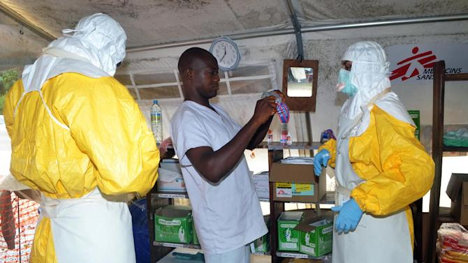 Members of Doctors Without Borders (MSF) put on protective gear at the isolation ward of the Donka Hospital in Guinea's capital Conakry on July 23, 2014 during the Ebola outbreak