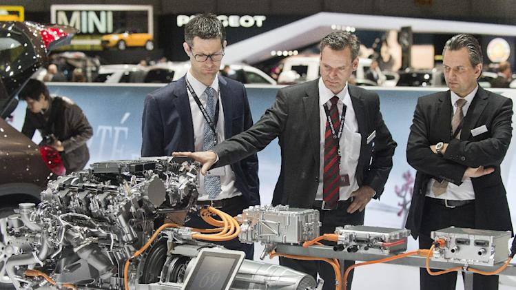 Journalists take a look at a Mercedes engine during the press day at the 84th Geneva International Motor Show in Geneva, Switzerland, Wednesday, March 5, 2014. (AP Photo/Keystone, Sandro Campardo)
