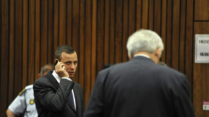 Olympic and Paralympic track star Oscar Pistorius talks on a mobile phone as he makes his way to the dock in the North Gauteng High Court in Pretoria