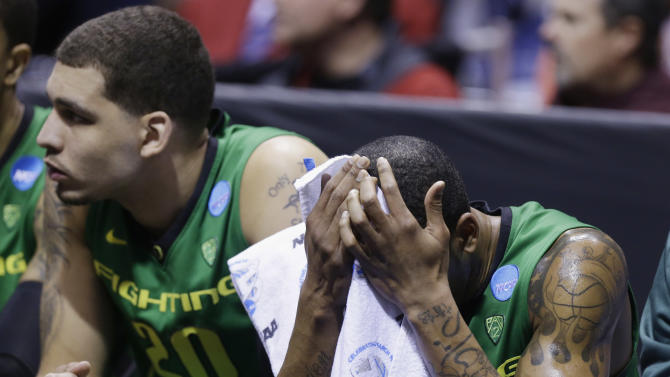 Oregon forward Carlos Emory holds his head down as he is benched during the second half of a regional semifinal against Louisville in the NCAA college basketball tournament, Friday, March 29, 2013, in Indianapolis. At left is center Waverly Austin (20). Louisville won 77-69. (AP Photo/Michael Conroy)