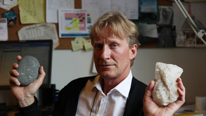 In this July 28, 2011 photo, geologist Sigurdur Reynir Gislason, the CarbFix experiment's chief scientist, holds examples of basalt rock, left, and limestone in his office at the University of Iceland in Reykjavik, Iceland. At a nearby geothermal plant, CarbFix scientists will separate carbon dioxide from a volcanic field's steam and pump it underground to react with porous basalt, forming limestone, to see how well the gas most responsible for global warming can be locked away in harmless form. (AP Photo/Brennan Linsley)