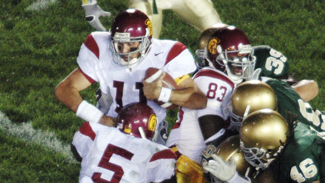 FILE - In this Oct. 15, 2005, file photo, Southern California running back Reggie Bush (5) pushes quarterback Matt Leinhart (11) into the end zone for a touchdown during an NCAA college football game against Notre Dame in South Bend, Ind. Leinart's winning touchdown with 3 seconds left gave Southern California a 34-31 victory. The Associated Press takes a look at some of the memorable games in college football's greatest intersectional rivalry in anticipation of Southern California hosting No. 1 Notre Dame on Saturday, Nov. 24, 2012. (AP Photo/Joe Raymond, File)