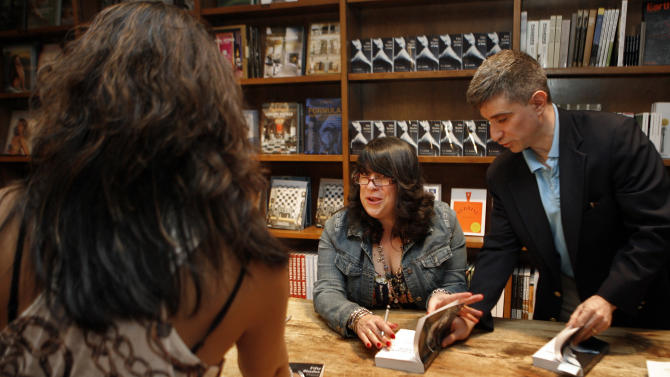 "Author E L James signs copies of her new erotic fiction book ""Fifty Shades of Grey"" with publicist Russell Perreault during a book signing in Coral Gables, Fla., Sunday, April 29, 2012. (AP Photo/Jeffrey M. Boan)"