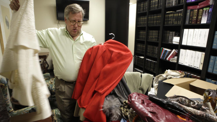 Legal media consultant Barry Pound sorts through a few of the gifts from the retailer Neiman Marcus given to Patricia Walker by her husband and now part of a lawsuit in Dallas, Thursday, May 31, 2012. Walker has sued the luxury store chain Neiman Marcus after unsuccessfully trying to return $1.4 million worth of jewelry, clothes and other items she claims her now ex-husband bought for her from an employee he was having an affair with. Walker claims the employee received a hefty commission from the sales and the store knew about the illicit arrangement. (AP Photo/LM Otero)