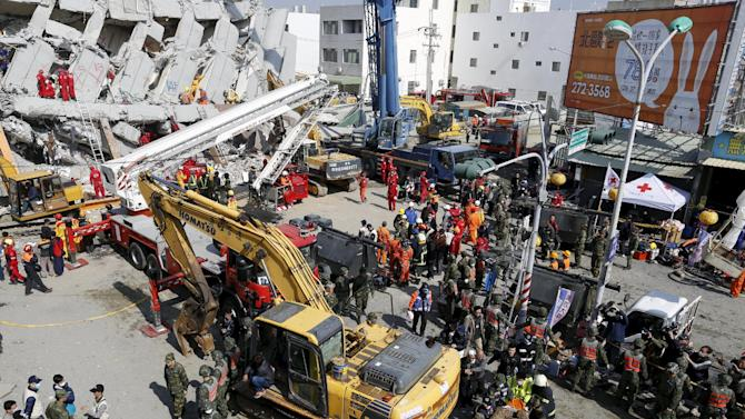 Rescue workers transport a body from the site where a 17-story apartment building collapsed after an earthquake hit Tainan, southern Taiwan