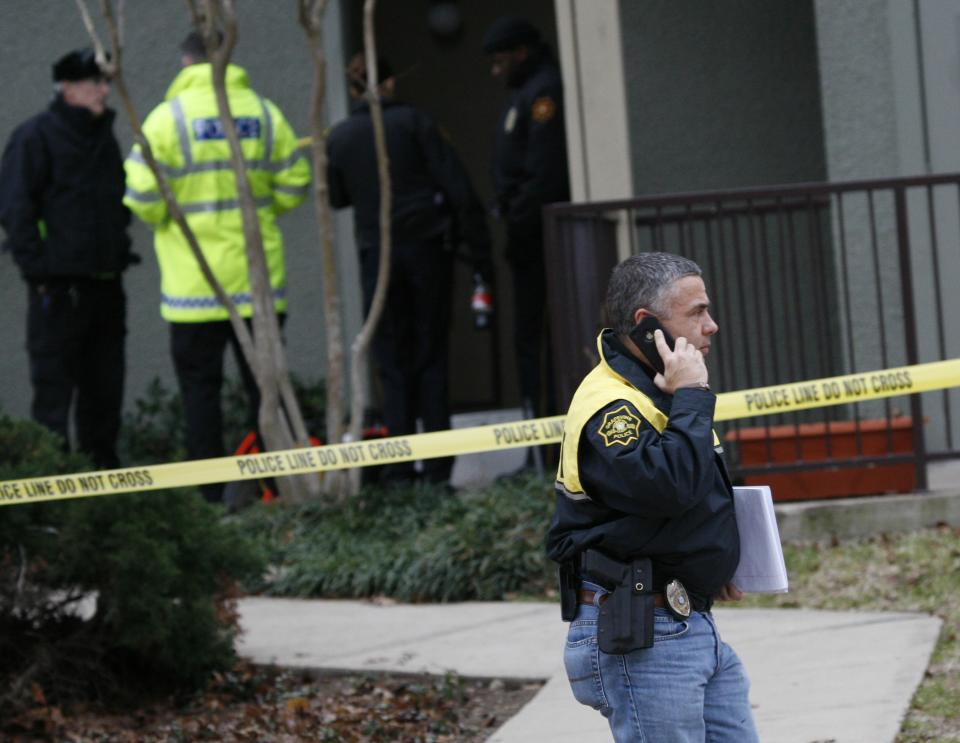 Grapevine police investigate the scene where they found seven people dead outside Dallas in Grapevine, Texas, Sunday, Dec. 25, 2011. Four women and three men who police believe to be related were found apparently shot to death, and authorities said they believe the shooter is among the dead. (AP Photo/Mike Fuentes)
