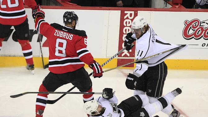 Los Angeles Kings' Justin Williams falls near  Anze Kopitar, of Slovenia, and New Jersey Devils' Dainius Zubrus, of Lithuania, in the first period during Game 5 of the NHL hockey Stanley Cup finals, Saturday, June 9, 2012, in Newark, N.J.. (AP Photo/Frank Franklin II)