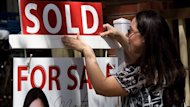 """A real estate agent puts up a """"sold"""" sign in front of a house in Toronto Tuesday, April 20, 2010. THE CANADIAN PRESS/Darren Calabrese"""