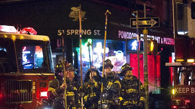 Firefighters look up towards 41 Spring Street in lower Manhattan after it was engulfed in a five alarm fire that had been contained, Thursday, Jan. 10, 2013, in New York. One person has died and eight people were injured. (AP Photo/John Minchillo)