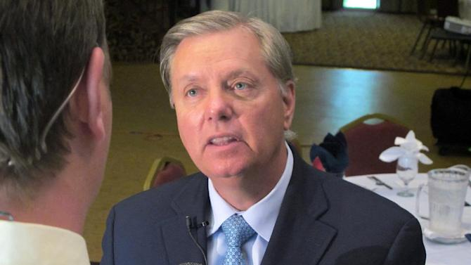 In this Sept. 3, 2013 photo, U.S. Sen. Lindsey Graham talks to a reporter following a speech to business leaders in Goose Creek, S.C. Graham is facing three challengers in the 2014 Republican primary for his seat. (AP Photo/Bruce Smith)