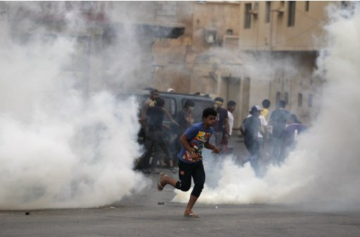 A protester runs through cloud of tear gas fired by riot-police during clashes after Arbaoon funeral procession of Abbas Habib west of Manama