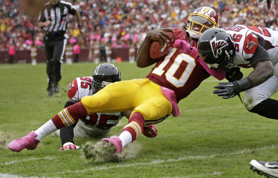 Washington Redskins quarterback Robert Griffin III is hit by Atlanta Falcons defensive end Jonathan Massaquoi (96) and defensive tackle Jonathan Babineaux (95) during the second half of an NFL football game in Landover, Md., Sunday, Oct. 7, 2012. (AP Photo/Evan Vucci)