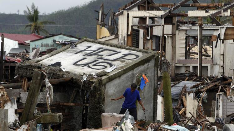 A victim of super typhoon Haiyan walks past a devastated area of San Jose town, Tacloban city, central Philippines