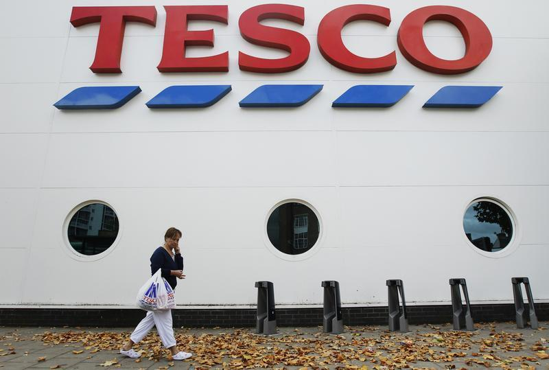 A shopper passes a Tesco supermarket in London