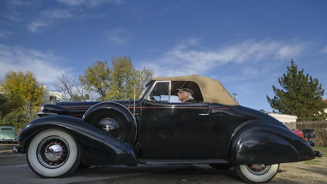 """In this photo taken Monday, Jan. 7, 2013, car collector, Garvin Kotzin, 63, who owns several cars featured in the """"Gangster Squad"""" film, poses with his 1936 Oldsmobile convertible in Los Angeles. To bring the story of mobster Mickey Cohen's reign over post-war Los Angeles to life, the director of """"Gangster Squad"""" employed Sean Penn, Josh Brolin, Ryan Gosling and more than 100 irreplaceable vintage American cars. (AP Photo/Damian Dovarganes)"""