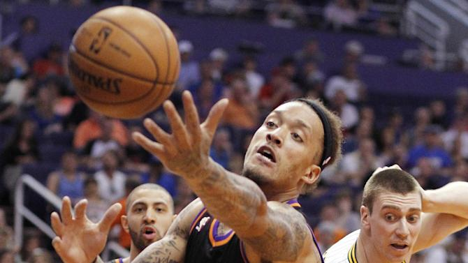 FILE - In this March 30, 2013, file photo, Phoenix Suns forward Michael Beasley, center, struggles to gain control of the ball against the Indiana Pacers in an NBA basketball game in Phoenix. The Suns and Beasley have reached an agreement to terminate the contract of the troubled power forward. The move on Tuesday Sept. 3, 2013 will cost the franchise $7 million, a $2 million savings from what Beasley would have been due had he simply been waived. It also represents a significant reduction in what the hit on the team's salary cap would have been. (AP Photo/Paul Connors, File)