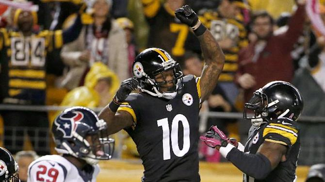 Pittsburgh Steelers wide receiver Martavis Bryant (10) celebrates with running back Le'Veon Bell (26) after making a touchdown catch as Houston Texans defensive back Andre Hal (29) walks by in the second quarter of the NFL football game, Monday, Oct. 20, 2014 in Pittsburgh