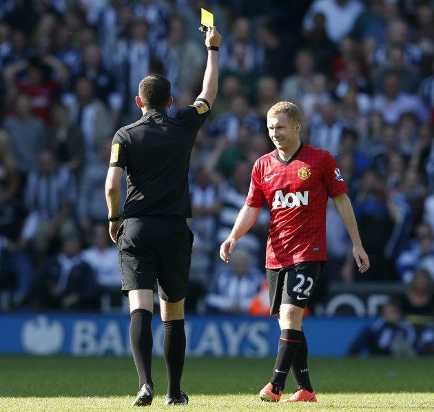 Manchester United's Paul Scholes smiles as he is given a yellow card in West Bromwich