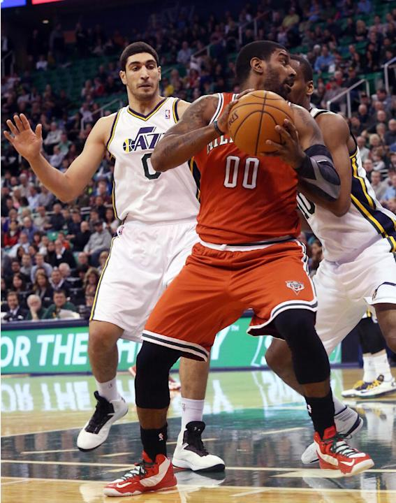 Milwaukee Bucks' O.J. Mayo (00) looks for the basket as he is defended by Utah Jazz's Enes Kanter (0) and Utah Jazz's Alec Burks, right, in the first half of an NBA basketball game Thursda