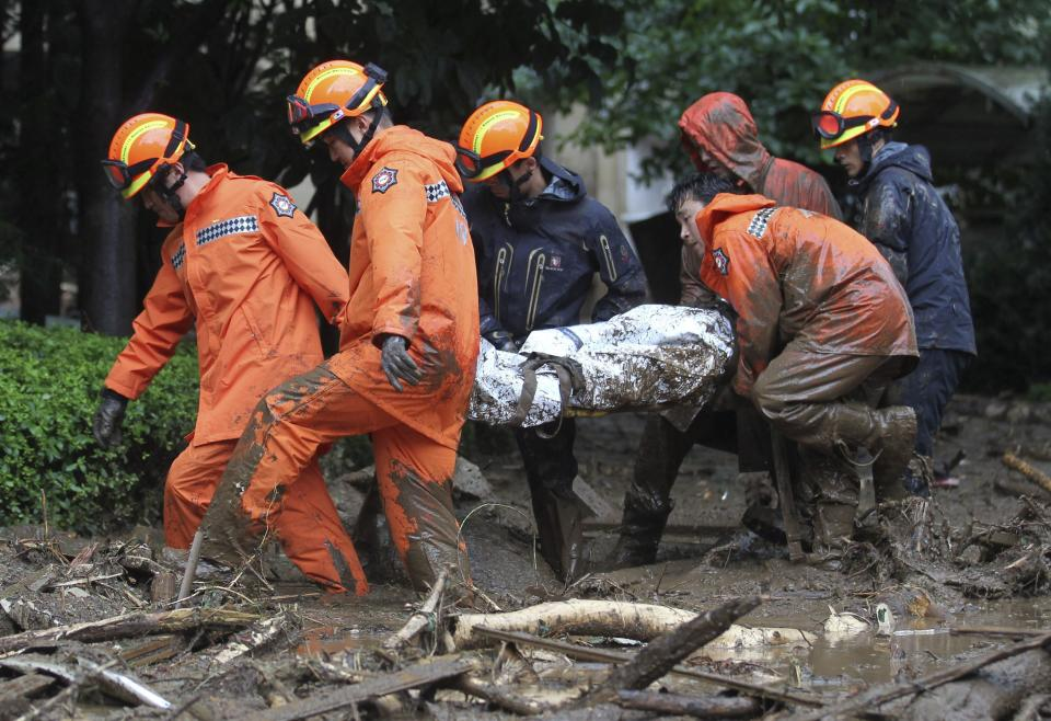 South Korean rescue workers carry a body after a landslide caused by heavy rains in Seoul, South Korea, Wednesday, July 27, 2011. A quick blast of heavy rain sent landslides barreling through South Korea's capital and a northern town Wednesday. (AP Photo/Yonhap, Kim Ju-sung)  KOREA OUT