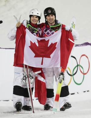 Canada's Alex Bilodeau, right, celebrates with compatriot Mikael Kingsbury after after Bilodeau won gold and Kingsbury took silver in the men's moguls final at the Rosa Khutor Extreme Park at the 2014 Winter Olympics, Monday, Feb. 10, 2014, in Krasnaya Polyana, Russia. (AP Photo/Andy Wong)