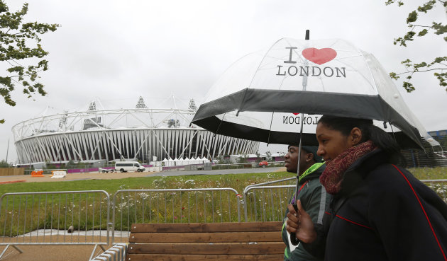 Pedestrians walk past Olympic Stadium in Stratford, east London
