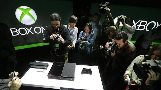 FILE - In this May 21, 2013 file photo, photographers crowd around Microsoft Corp.'s next-generation Xbox One entertainment and gaming console system after it was officially revealed, at an event in Redmond, Wash. When it comes to hyping the latest hardware, the video game industry doesn't typically opt for simplicity. However, during a presentation to promote the upcoming Xbox One video game console at GameStop Expo in Las Vegas last week, a no-frills approach is exactly what Microsoft employed when confronted with a convention room full of passionate gamers. It's the first stop on an apology tour for Microsoft, which has continued to experience a backlash over connectivity and privacy concerns since unveiling the next-generation device in May. (AP Photo/Ted S. Warren, File)