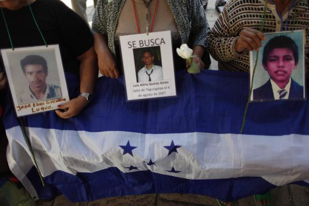 Central American women of the Caravan of Central American Mothers hold portraits of missing migrants against a Honduras flag as they arrive at Tultitlan