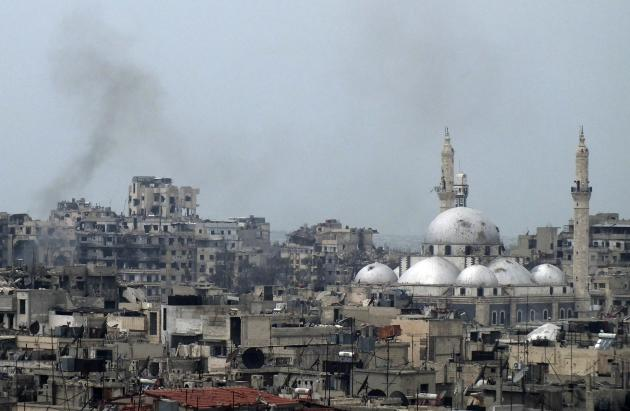 Smoke rises behind damaged buildings as the Khalid bin al Walid Mosque is seen on right in the besieged area of Homss