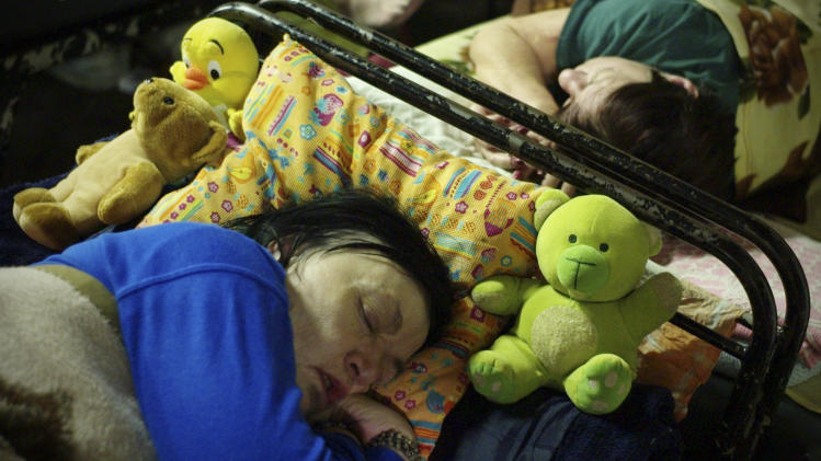 In this photo taken early morning Friday, Jan. 11, 2013, homeless women sleep with their teddy-bears in a shelter called 'The Heated Street' in Budapest, Hungary. Hungary considers constitutional change to allow authorities to force homeless off the streets. (AP Photo/Bela Szandelszky)